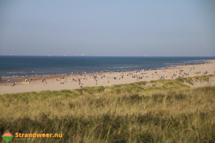 Drukke stranddag door warm herfstweer