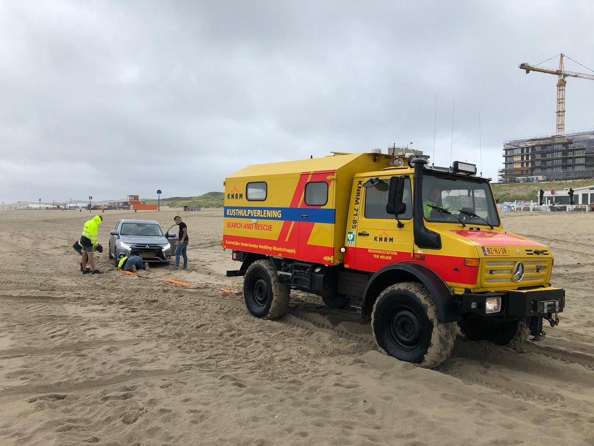 Automobilist gestrand op het strand